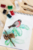 Still life with childish watercolor painting of bullfinch Stock Photo