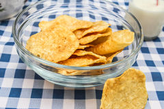Still Life with Chips and Milk. A Still Life of Potato Chips in a glass bowl, with a bottle of milk on a blue and white checked cloth Royalty Free Stock Photos