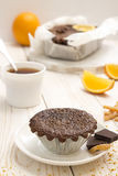 Still life with chocolate cupcake and cup of tea. Still life with chocolate cupcake with dried orange peels, chocolate cake in parchment paper, cup of tea Stock Photo