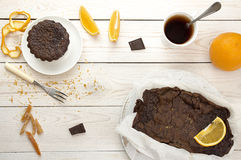 Still life with chocolate cupcake and cup of tea. Still life with chocolate cupcake with dried orange peels, chocolate cake in parchment paper, cup of tea Royalty Free Stock Photo