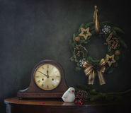 Still life with a Christmas wreath, old clocks, and a white porcelain bird. With fir branches and cones, red berries in the background, at a round table and a stock photography