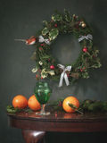 Still life with Christmas wreaths, green glass and oranges. Still life with Christmas wreaths, green and orange glass, hand made wreath of fir branches, red royalty free stock photos