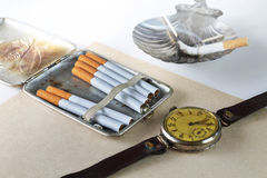 Still life with a cigarette case. Hours and cigarettes in a retro style Stock Photos