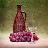 Still-life with clay bottle, glass and grapes Royalty Free Stock Image
