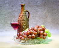 Still-life with clay bottle, grapes and glass Stock Image