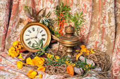 Still life. With clock, old oil lamp, sea-buckthorn and mushrooms Royalty Free Stock Photo