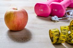 Fitness and diet a new concept. Still life and close up with apple, pink weight, yellow tape measure. fitness and lifestyle concepts Royalty Free Stock Image
