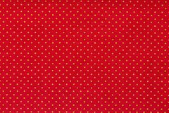 Still life close up detail of a bright red piece of paper with aligned white polka dots and texture. royalty free stock photo