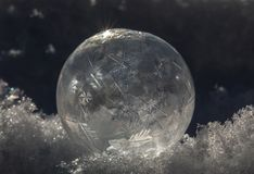 Close-up of Frozen Soap Bubble with Ice Crystals in Snow. Still-life Close-up of Frozen Soap Bubble with Ice Crystals in Snow with light and shadows Royalty Free Stock Photos