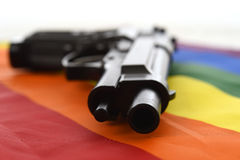Still life with close up gun resting on gay parade flag representing sexual discrimination and intolerance Royalty Free Stock Image