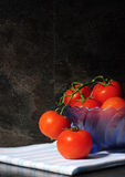 Still life closeup of bright red tomatoes in blue vintage bowl Stock Photo
