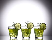 Still life with colorful bright cocktails on glass, decorated with rosemary and lime Royalty Free Stock Images