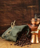 Still life coffee beans in a bag and copper pot Stock Image