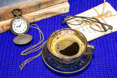 Still life with coffee on a blue knitted background. Coffee, pictures, watches, glasses and old tattered books on a blue knitted background Stock Images