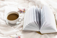Still-life coffee cup and a book in bed Stock Photo