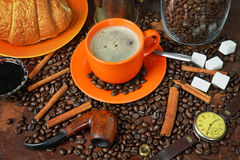 Still life on a coffee subject in a retro style. Still life with a cup of coffee, coffee grains, sugar, croissant and a tube for smoking Stock Photo