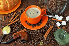 Still life on a coffee subject in a retro style. Still life with a cup of coffee, coffee grains, sugar, croissant and a tube for smoking Royalty Free Stock Photos
