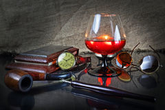 Still life with a cognac glass in a retro style. Still life with a cognac glass, hours, a tube for smoking, points and a fountain pen in a retro style Royalty Free Stock Photo