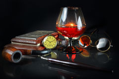 Still life with a cognac glass in a retro style. Still life with a cognac glass, hours, a tube for smoking, points and a fountain pen in a retro style Stock Photos