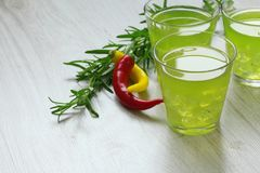 Still life with colorful bright cocktails on wooden background, chilli pepper and rosemary near Royalty Free Stock Image