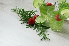 Still life with colorful bright cocktails on wooden background, decorated with rosemary, strawberry and lime Stock Photography