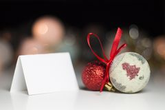 Still life with colorful christmas balls and blank paper card fo. R your text - photo with selective focus Royalty Free Stock Photo