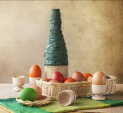 Still life colorful Easter eggs basket vase royalty free stock photos