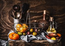 Still life with colorful organic tomatoes in harvesting basket, kitchen utensils, olives oil bottle on dark wooden stock image