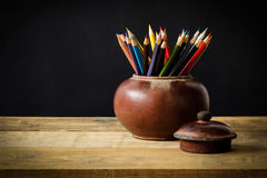 Still life with colour pencils in old clay jar Royalty Free Stock Photo