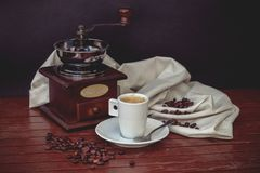 Do you want some coffee?. Still-life composed by coffee elements like a cup, spoon, plate, coffee grinder, grains and a cloth in a wood table, all in a classic Royalty Free Stock Image