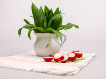 Still life composition with bear's garlic (Allium Ursinum) and radishes. Still life composition with bear's garlic (Allium Ursinum) leaves and buds and sliced Stock Photography