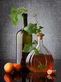 Still life composition with bottles leafs and mandarins on dark. Background royalty free stock photography