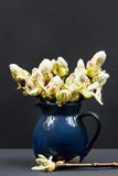 Still life composition with chestnut buds, flowers and small leaves in a blue ceramic pot Stock Photo
