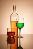 Still life composition with glasses and bottle filled with color. Ed liquids royalty free stock photography