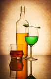 Still life composition with glasses and bottle filled with color. Ed liquids on light textured background stock photography