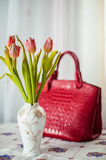Still life composition, in home interior on the table with a tablecloth, tulips in a beautiful vase on a background of red ladies` Stock Photography