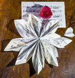 Still life composition made with a musical score folded in the shape of a flower and a red rose royalty free stock image