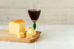 Red wine and a piece of cheese. Still life composition with red wine and homemade rustic cheese Royalty Free Stock Photography