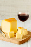 Red wine and a piece of cheese. Still life composition with red wine and homemade rustic cheese Royalty Free Stock Photo