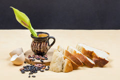 Still life composition with wooden kitchen cutting board, beans, egg shell, bread and ceramic pot with Arum flower Royalty Free Stock Photo