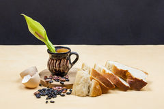Still life composition with wooden kitchen cutting board, beans, egg shell, bread and ceramic pot with Arum flower Royalty Free Stock Images