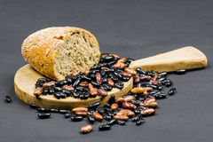 Still life composition with wooden kitchen cutting board, black and brown beans and organic bread Royalty Free Stock Images