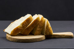 Still life composition with wooden kitchen cutting board and slices of bread Stock Photo