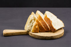 Still life composition with wooden kitchen cutting board and slices of bread Royalty Free Stock Photo