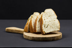 Still life composition with wooden kitchen cutting board and slices of bread Stock Photography