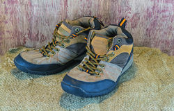 Still- life concept hiking boots or outdoor shoes on sack sisal Stock Images