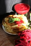 Still life. A still-life consisting of appetizing pear fritters, sprinkled with raspberry jam and decorated with mint leaves, in the background a creamer with Stock Image