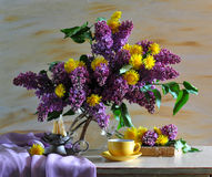 still life consisting of  lilac and dandelions Royalty Free Stock Photos