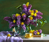 Still life consisting of  lilac and dandelions Royalty Free Stock Photo