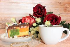 Still life. A still life consisting of a piece of a festive cake on a white plate and red roses with golden beads on a lacy white napkin and white cup of tea on Royalty Free Stock Image